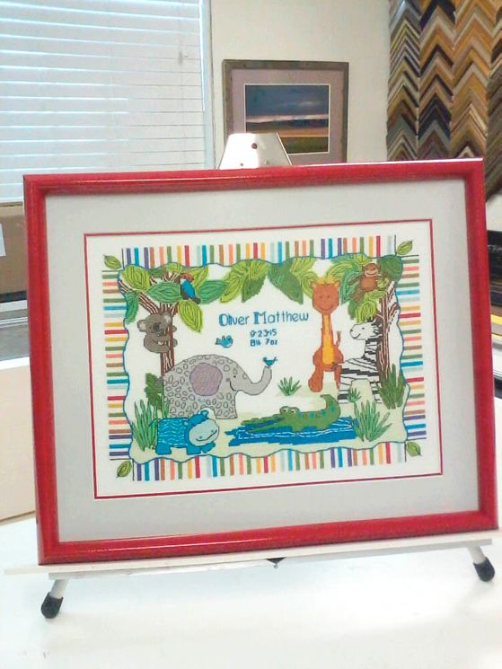 Beautiful Cross Stitch celebrating a baby's arrival and using one of our high-gloss, brightly colored frames for fun in a nursery.